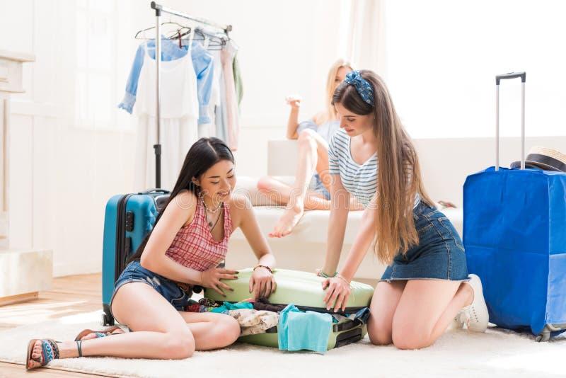 młode kobiety pakuje walizki dla wakacje pakuje wpólnie w domu zdjęcie royalty free