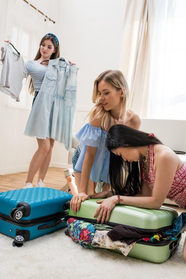 młode kobiety pakuje walizki dla wakacje pakuje wpólnie w domu zdjęcie stock