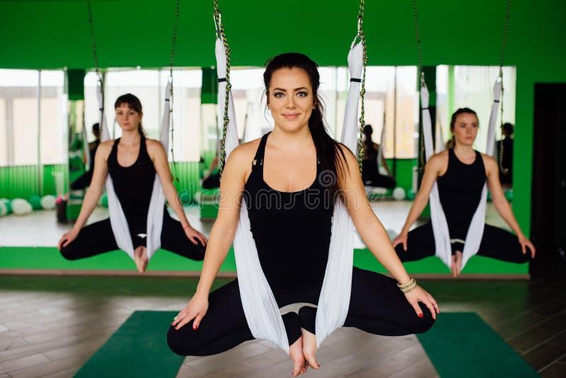 Młode kobiety robi antigravity joga ćwiczą z grupą ludzi aero komarnicy sprawności fizycznej trenera trening biali hamaki zdjęcia royalty free