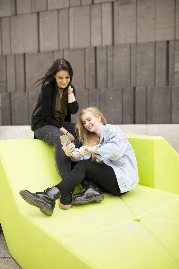 Młode kobiety siedzi w mieście i używają telefon komórkowego zdjęcie stock