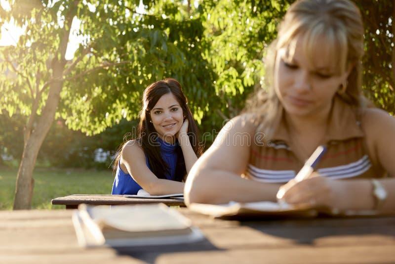 Młode kobiety studiuje z podręcznikiem dla szkoła wyższa egzaminów przy szkołą zdjęcia stock