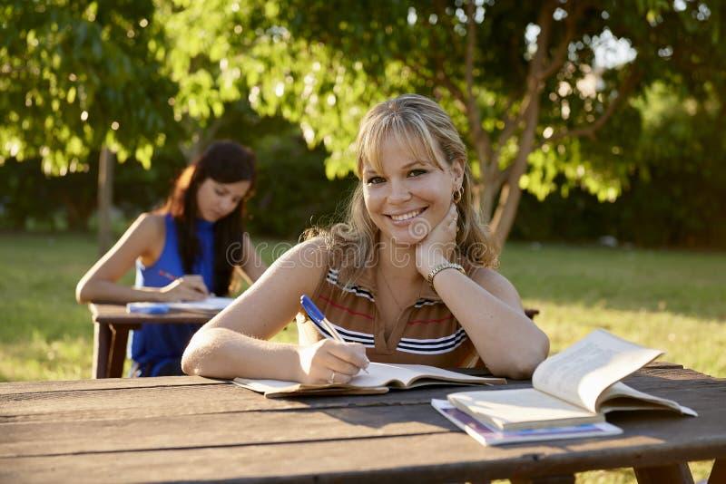 Młode kobiety studiuje z podręcznikiem dla szkoła wyższa egzaminów przy szkołą fotografia stock