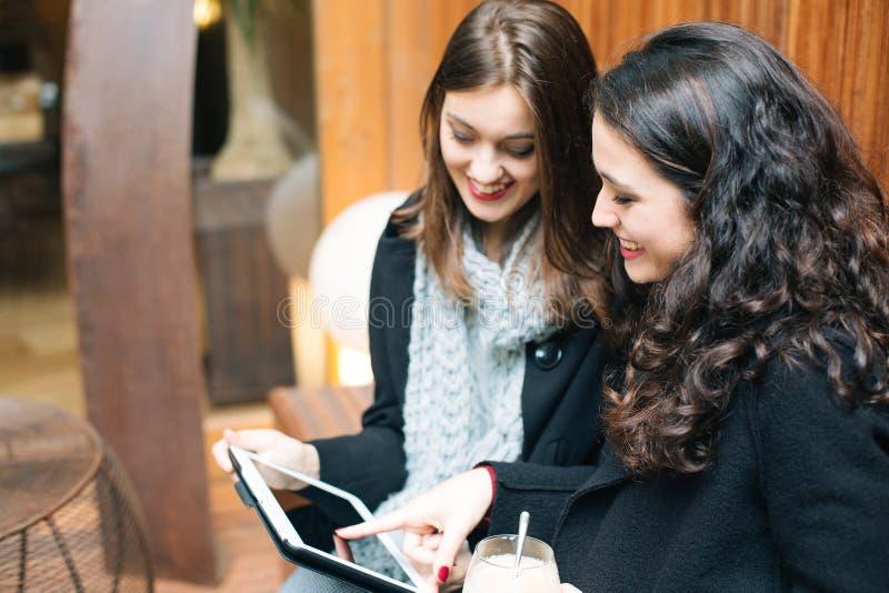 Młode kobiety używa pastylkę w kawiarni zdjęcia stock