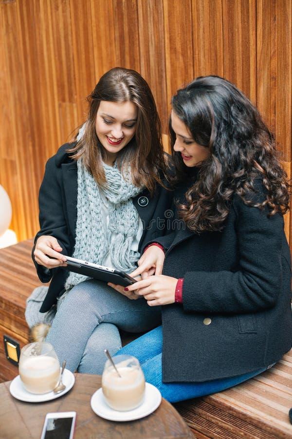Młode kobiety używa pastylkę w kawiarni zdjęcie royalty free