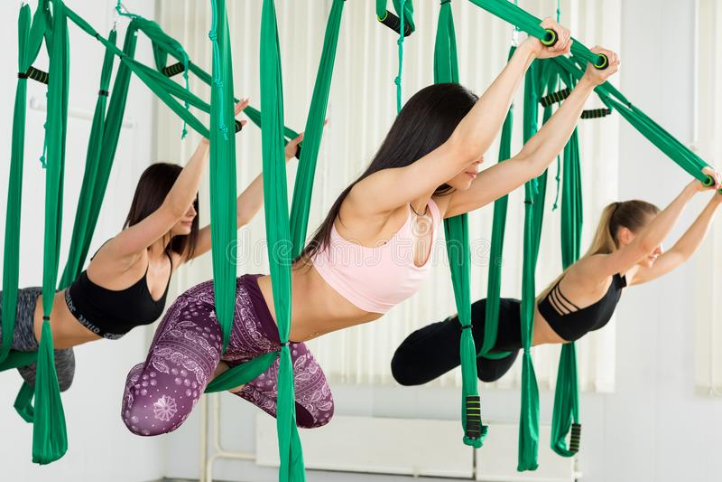 Młode kobiety wykonuje antigravity joga ćwiczenie obrazy royalty free