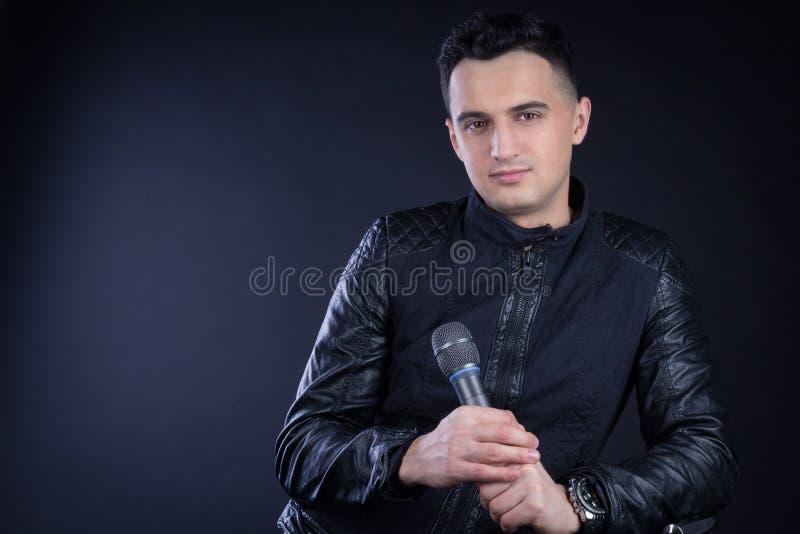 Młode męskie czarnogłowe wystrzału piosenkarza pozy z mikrofonem obraz royalty free