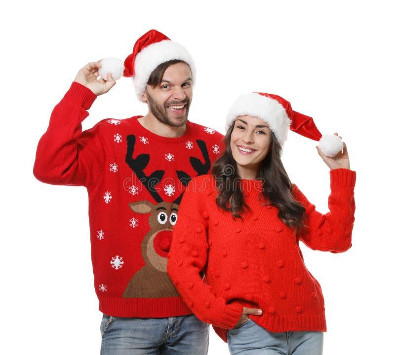 MÅ'ode pary w Å›wiÄ…tecznych swetrach i kapeluszach na biaÅ'o zdjęcia stock