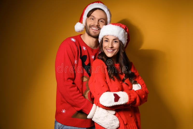 Młode pary w Boże Narodzenie i kapelusze na żółtym tle obrazy royalty free