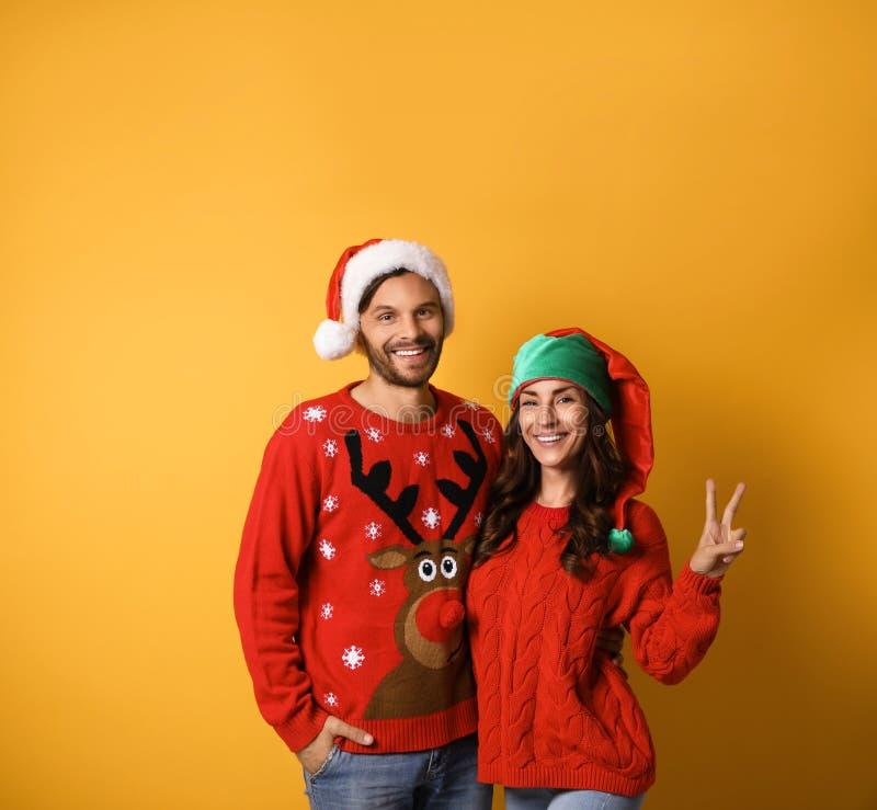 Młode pary w swetrach świątecznych na żółtym tle fotografia royalty free