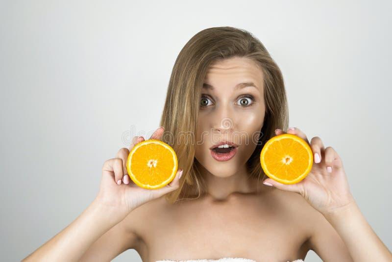 Młode piękne blond kobiety mienia pomarańcze w jej rękach patrzeje zaskakującego odosobnionego białego tło zdjęcia royalty free