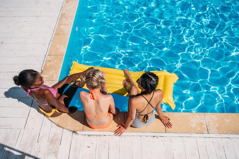 Młode piękne wieloetniczne kobiety siedzi blisko pływackiego basenu zdjęcie royalty free