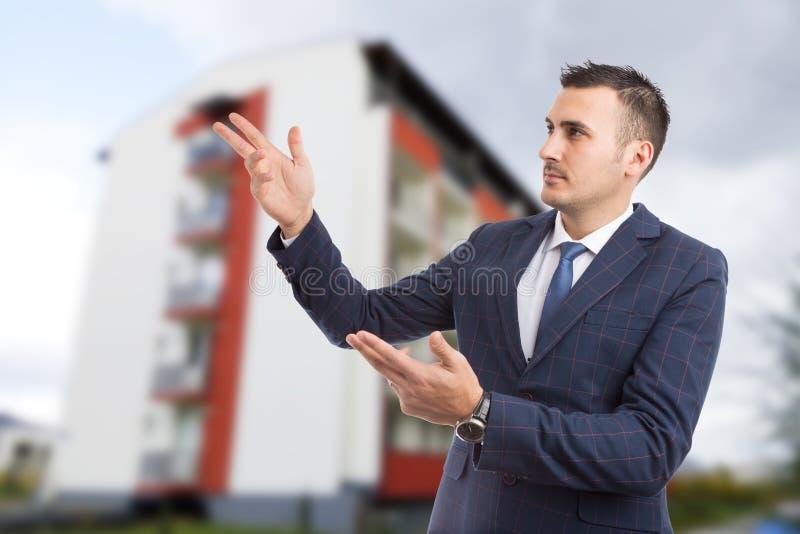 Młode pośrednika handlu nieruchomościami lub agenta nieruchomości mienia ręki w przedstawiać g zdjęcie stock