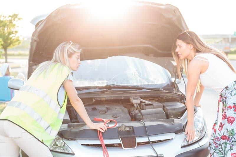 młode samochód łamane kobiety dwa Patrzejący parowozowej zatoki z kapiszonem otwiera zdjęcia stock