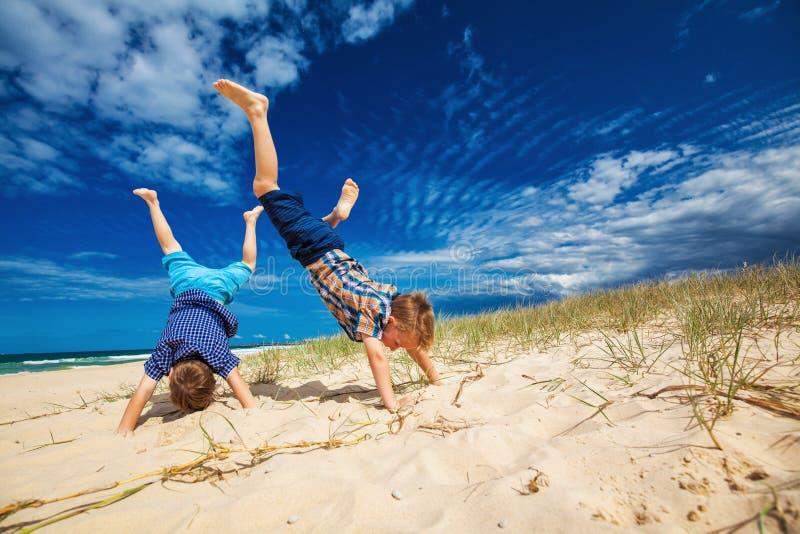 Młode szczęśliwe chłopiec ma zabawę na tropikalnej plaży, robi ręka stojakom fotografia stock