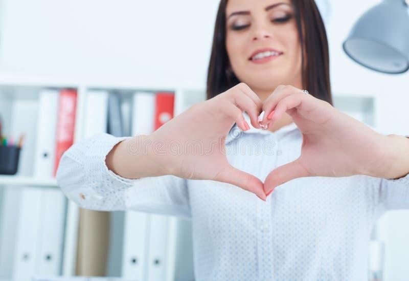 Młode uśmiechnięte żeńskie urzędnika przedstawienia serca ręki kochają naszych klientów obrazy stock