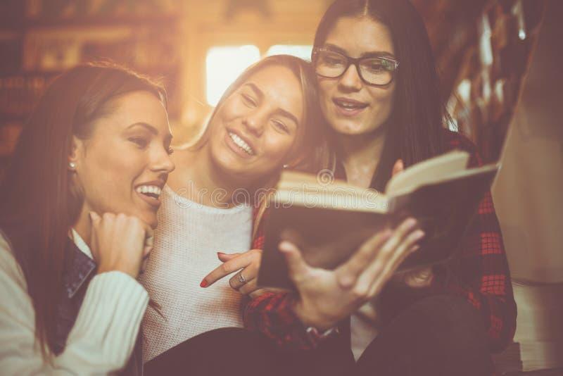 Młode uczeń dziewczyny w bibliotecznej czytelniczej książce wpólnie clo obraz stock