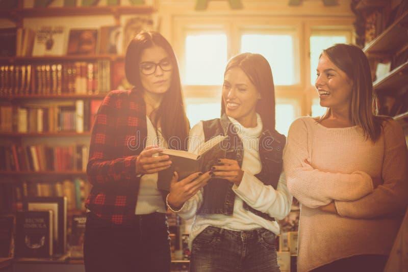 Młode uczeń dziewczyny w bibliotecznej czytelniczej książce wpólnie i obraz royalty free