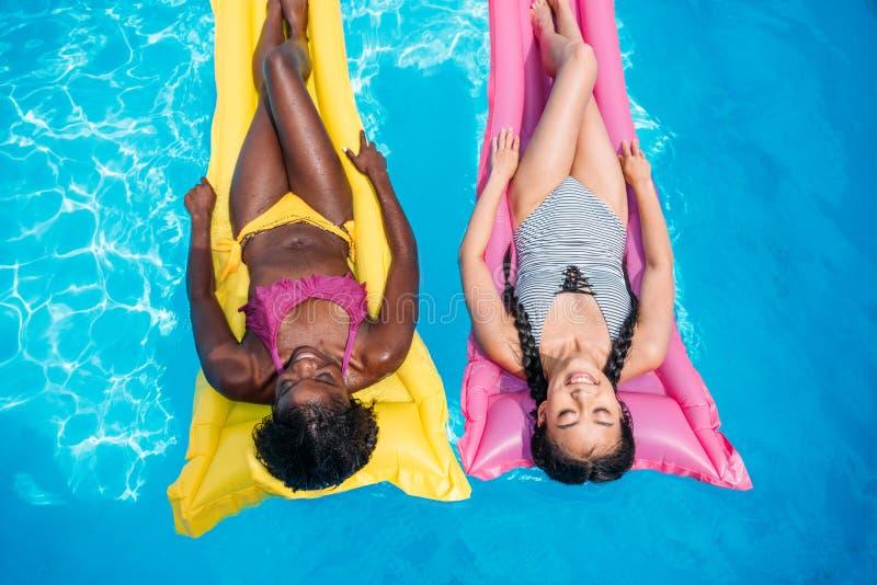 Młode wieloetniczne kobiety unosi się na nadmuchiwanych materac w pływackim basenie obraz royalty free