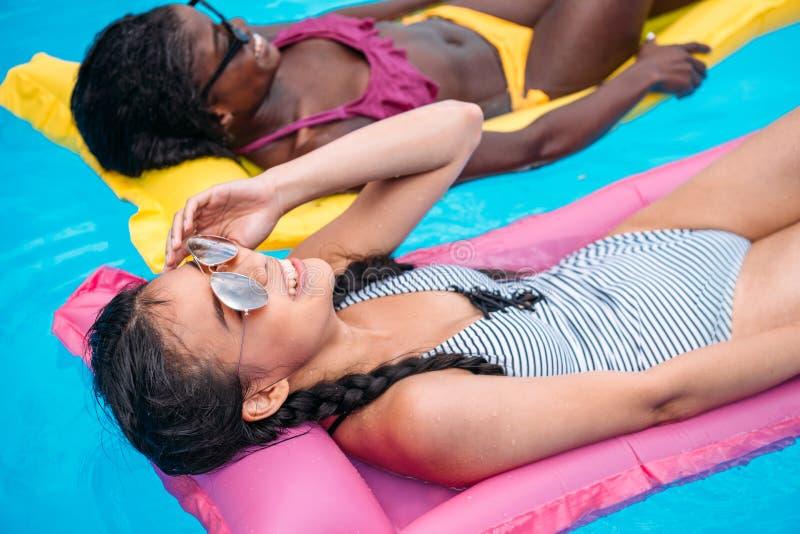 Młode wieloetniczne kobiety unosi się na nadmuchiwanych materac w pływackim basenie zdjęcie stock