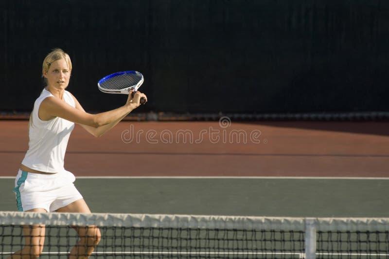 Młodego żeńskiego gracz w tenisa kołyszący kant przy sądem fotografia royalty free