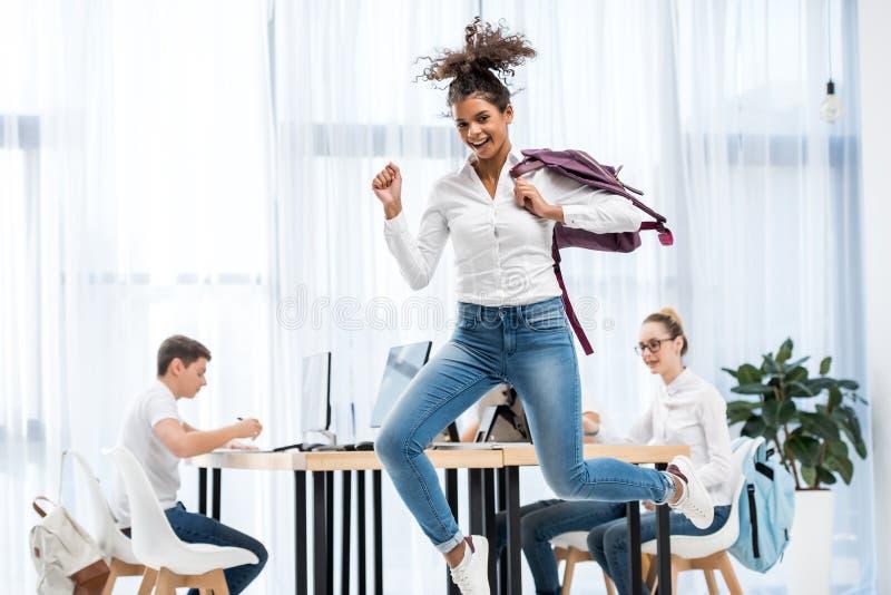 młodego amerykanin afrykańskiego pochodzenia dziewczyny studencki doskakiwanie w sali lekcyjnej zdjęcie royalty free