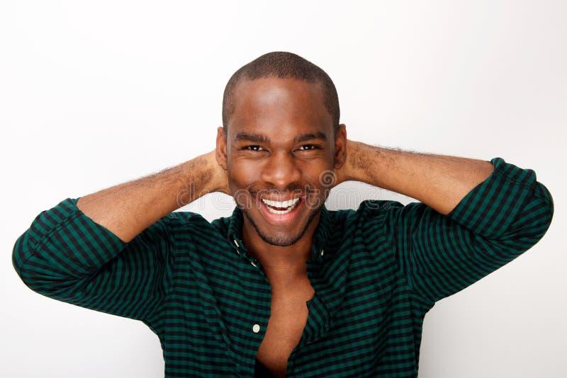 Młodego amerykanin afrykańskiego pochodzenia mody męski model ono uśmiecha się z rękami za głową przeciw odosobnionemu białemu tł obraz royalty free