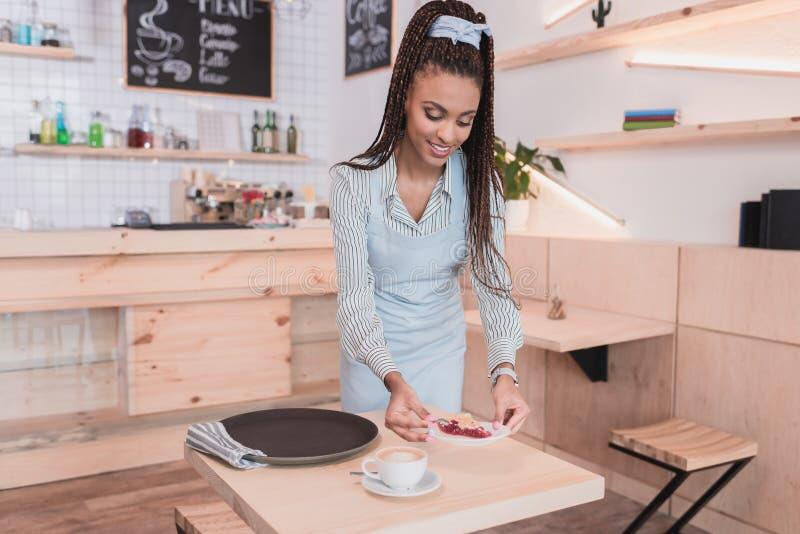Młodego amerykanina afrykańskiego pochodzenia barista słuzyć filiżanka kawy i kulebiak stół obraz royalty free