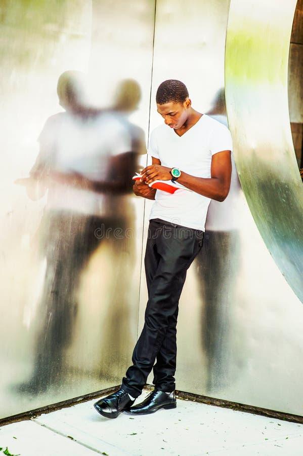 Młodego amerykanina afrykańskiego pochodzenia mężczyzna Czytelnicza książka outside w Nowy Jork fotografia royalty free