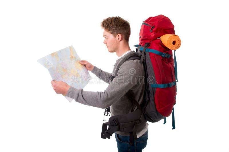 Młodego atrakcyjnego backpacker turystyczna przyglądająca mapa niesie dużego plecaka lugagge zdjęcie stock