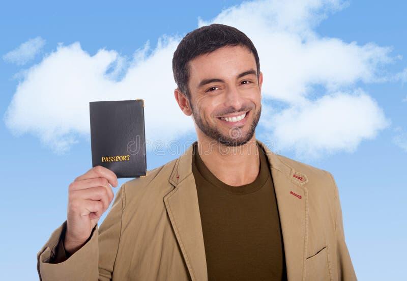 Młodego atrakcyjnego podróżnika mężczyzna mienia paszportowy ono uśmiecha się szczęśliwy i ufny zdjęcie stock