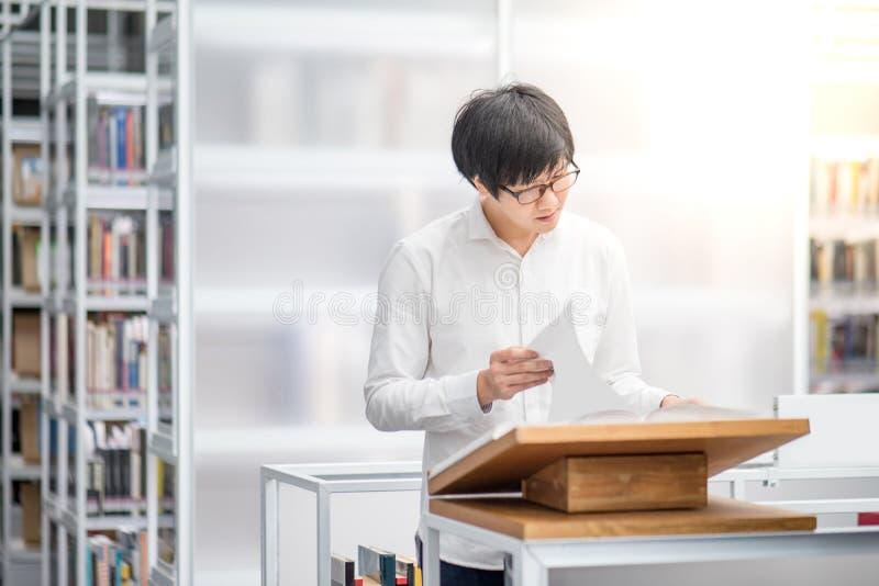 Młodego Azjatyckiego studenta uniwersytetu czytelnicza książka w bibliotece fotografia stock
