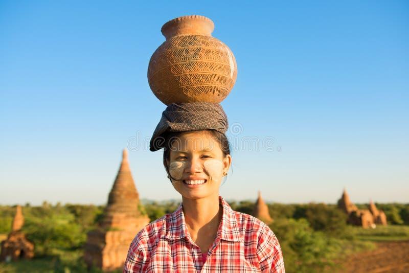 Młodego Azjatyckiego tradycyjnego żeńskiego średniorolnego przewożenia gliniany garnek na głowie zdjęcie stock