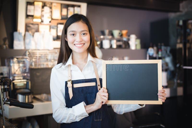 Młodego azjatykciego kobiety barista mienia chalkboard pusty menu w coffe zdjęcia stock