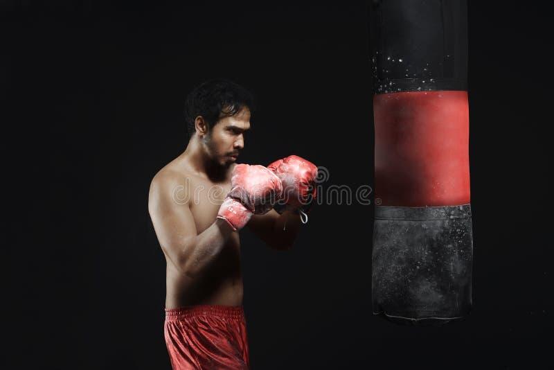 Młodego azjatykciego mężczyzna bokserski trening z uderzać pięścią torbę zdjęcie stock