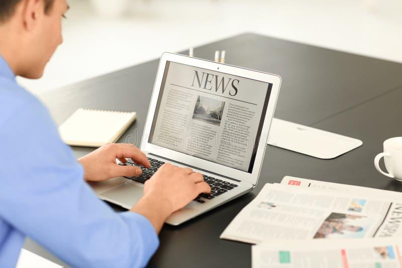 Młodego biznesmena czytelnicza wiadomość na laptopu ekranie w biurze obraz royalty free
