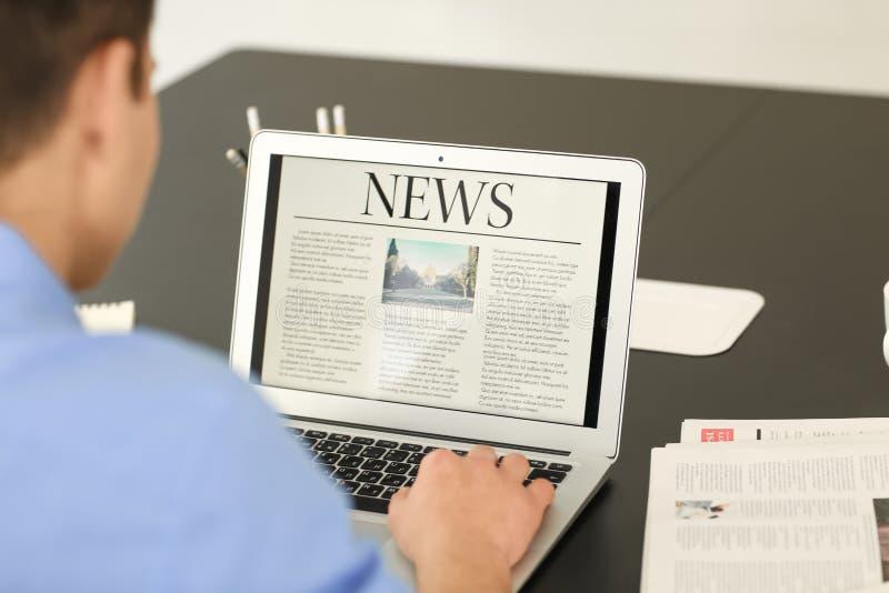 Młodego biznesmena czytelnicza wiadomość na laptopu ekranie w biurze zdjęcie stock