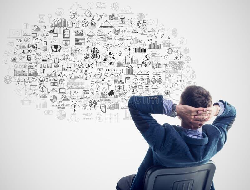 Młodego biznesmena siedzący główkowanie marzy wokoło zdjęcie stock