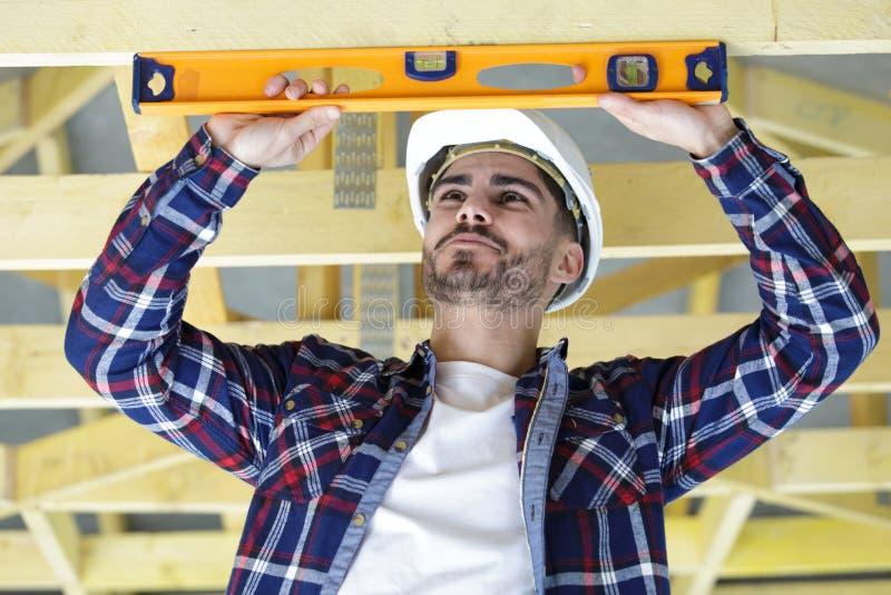 Młodego budowniczego sprawdza promień z spirytusowym poziomem zdjęcie stock