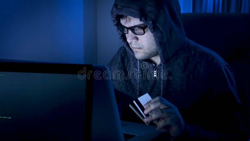 Młodego cyber kryminalny działanie na programa kodzie dla kraść pieniądze od kredytowych kodów zdjęcia royalty free