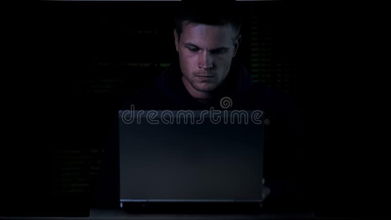 Młodego cyber międlenia systemu ochrony kryminalny siedzący laptop, wirtualny wirusowy kod zdjęcie stock