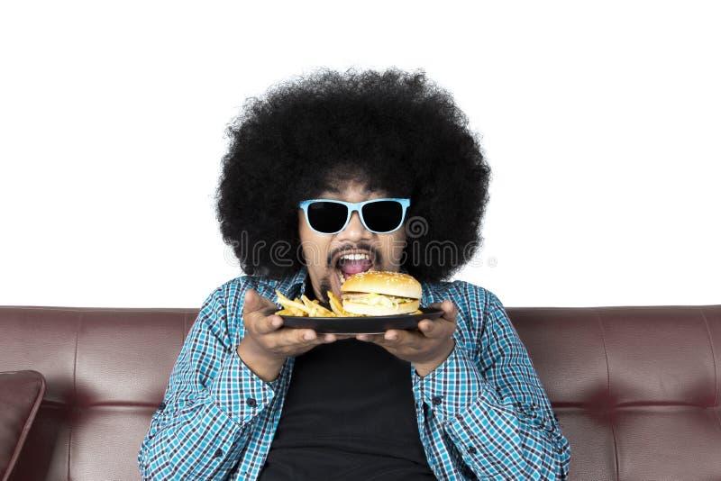 Młodego człowieka łasowania francuza i hamburgeru dłoniaki fotografia royalty free