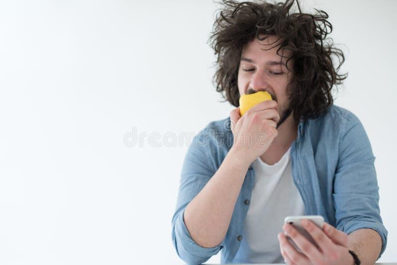 Młodego człowieka łasowania jabłko i używać telefon komórkowego w domu zdjęcia stock