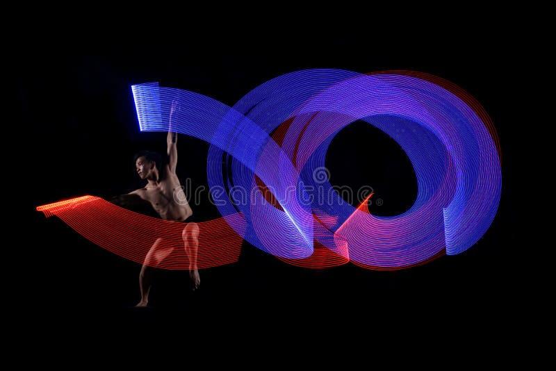 Młodego człowieka baletniczy taniec z błękita i czerwonych świateł skutkiem zdjęcia royalty free