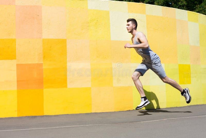 Młodego człowieka bieg przeciw jaskrawej ścianie zdjęcie royalty free