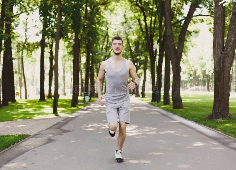 Młodego człowieka bieg w zieleń parku, kopii przestrzeń obraz stock