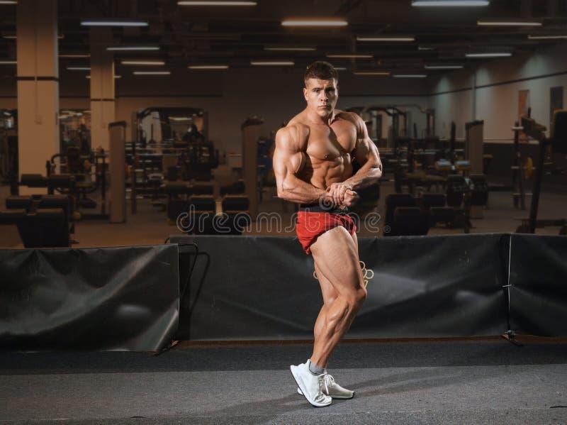 Młodego człowieka bodybuilder pozycja w gym i pozować zdjęcie royalty free