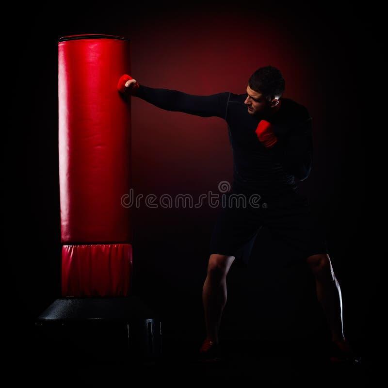 Młodego człowieka boksu hittingby torba w studiu fotografia royalty free