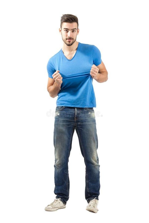 Młodego człowieka ciągnięcie lub drzeć koszulka zdjęcie stock