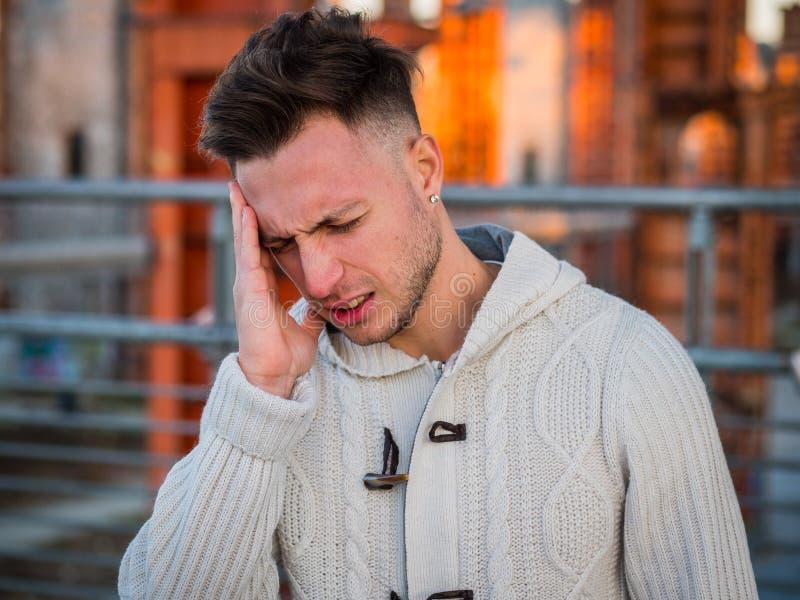 Młodego człowieka cierpienie od migreny, plenerowej w mieście obrazy stock