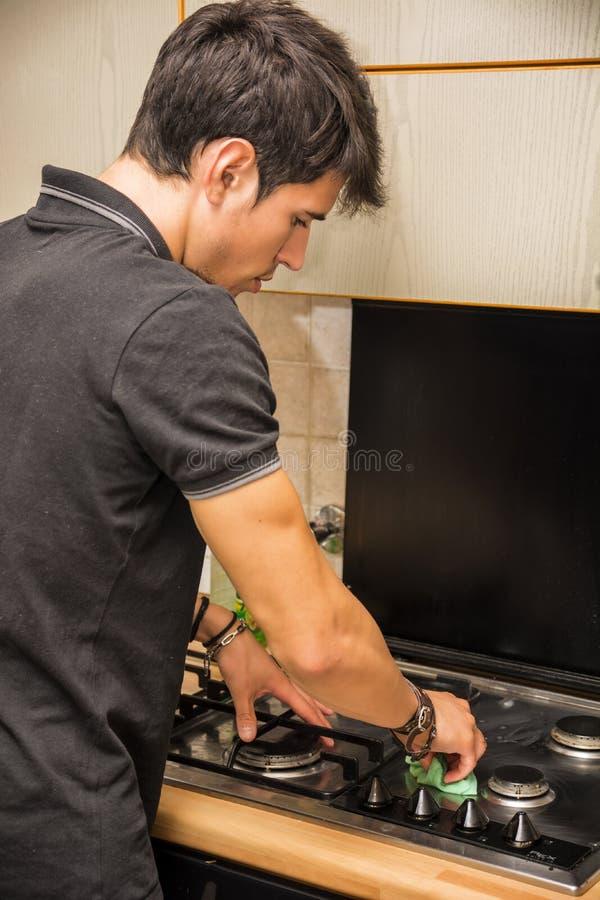 Młodego Człowieka Cleaning kuchenki wierzchołek z gąbką zdjęcia stock